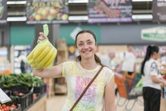 Menina feliz comprada bananas na loja Mulher de sorriso com bananas à disposição blurry imagens de stock