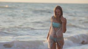 A menina feliz corre ao longo da praia e aprecia vídeos de arquivo