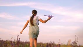 A menina feliz corre com um avião do brinquedo em um campo de flor as crian?as jogam o avi?o do brinquedo Sonhos do adolescente d video estoque