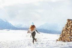 A menina feliz corre na primeira neve imagens de stock