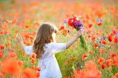 Menina feliz da criança com as flores selvagens que rodam-se no prado no verão Fotos de Stock