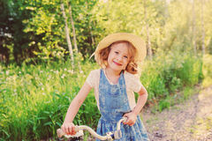 Menina feliz da criança com a bicicleta na estrada ensolarada do verão Fotografia de Stock Royalty Free