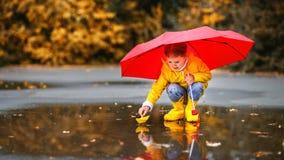 Menina feliz da criança com o barco do guarda-chuva e do papel na poça na fotos de stock royalty free