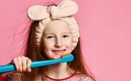 Menina feliz da criança com os dentes das escovas da escova de dentes fotos de stock