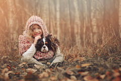 Menina feliz da criança com seu cão do spaniel na caminhada morna acolhedor do outono