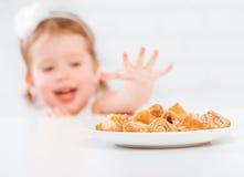 A menina feliz da criança come cookies e leite imagens de stock royalty free