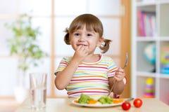 A menina feliz da criança come os vegetais que sentam-se na tabela imagens de stock