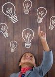 Menina feliz da criança do escritório que aponta acima contra o fundo de madeira com ícones dos bulbos Fotos de Stock Royalty Free