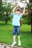 A menina feliz da criança está saltando no ar ao ar livre Fotografia de Stock Royalty Free