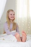 A menina feliz da criança está sentando-se na cama com os pés descalços Fotos de Stock
