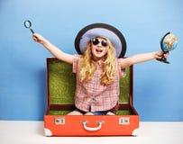 A menina feliz da criança está sentando-se na mala de viagem cor-de-rosa que guarda um globo e uma lupa Conceito do curso e da av imagens de stock