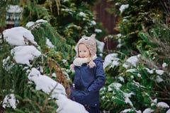A menina feliz da criança joga no jardim nevado do inverno Fotos de Stock Royalty Free
