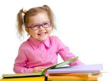 Menina feliz da criança no assento dos livros de leitura dos vidros fotografia de stock royalty free