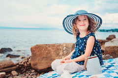 A menina feliz da criança no chapéu da listra que joga na praia e escuta o shell do mar fotografia de stock royalty free