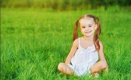 Menina feliz da criança no vestido branco que encontra-se no verão da grama Fotos de Stock Royalty Free