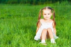 Menina feliz da criança no vestido branco que encontra-se no verão da grama Fotos de Stock
