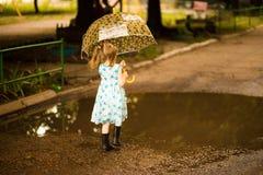 Menina feliz da criança no vestido com um guarda-chuva e umas botas de borracha na poça imagem de stock royalty free