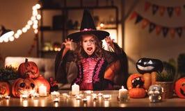 A menina feliz da criança nos trajes da bruxa em uma casa escura bendiz dentro foto de stock royalty free