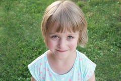 Menina feliz da criança pequena com olhos verdes que sorri e que olha na câmera, no prado verde borrado no fundo imagem de stock royalty free