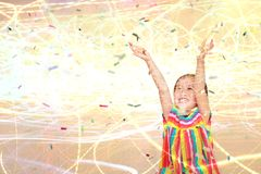 Menina feliz da criança pequena de exposição dobro com confetes coloridos e fundo claro Ano novo feliz ou conceito das felicitaçõ imagem de stock