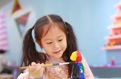 Menina feliz da criança pequena que tem o divertimento a pintar na boneca do estuque interno foto de stock