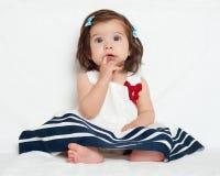 A menina feliz da criança pequena senta-se na toalha branca, na emoção feliz e na expressão da cara, surpreendidas muito, o dedo  Fotografia de Stock