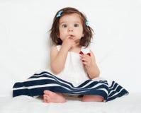 A menina feliz da criança pequena senta-se na toalha branca, na emoção feliz e na expressão da cara, surpreendidas muito, o dedo  Fotografia de Stock Royalty Free