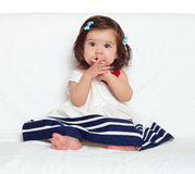 A menina feliz da criança pequena senta-se na toalha branca, na emoção feliz e na expressão da cara, surpreendidas muito, o dedo  Imagens de Stock Royalty Free