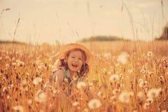 Menina feliz da criança que anda no prado do verão com dangelions Cena rural do estilo country, atividades exteriores imagens de stock royalty free