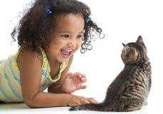 Menina feliz da criança que encontra-se no assoalho e que joga com foto de stock royalty free