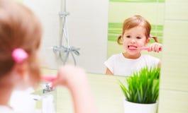 Menina feliz da criança que escova suas escovas de dentes dos dentes no banheiro Fotografia de Stock