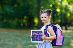 Menina feliz da criança que está com mesa e trouxa ou sacola Aluno no primeiro dia da classe elementar Saudável Imagens de Stock Royalty Free