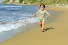 Menina feliz da criança que funciona na praia Foto de Stock