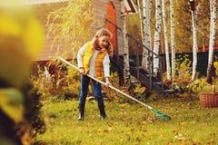 A menina feliz da criança que joga o jardineiro pequeno no outono e que escolhe sae na cesta Trabalho sazonal do jardim Imagem de Stock Royalty Free