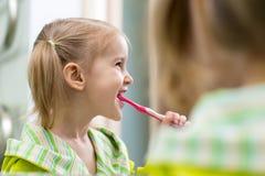 Menina feliz da criança que olha o espelho usando os dentes da limpeza da escova de dentes no banheiro cada manhã e noite fotografia de stock royalty free