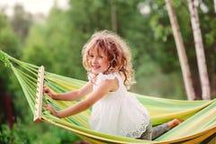 Menina feliz da criança que tem o divertimento e que relaxa na rede no verão Fotografia de Stock Royalty Free