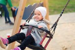 Menina feliz da crian?a no balan?o na queda do por do sol Criança que joga no outono no parque natural fotos de stock