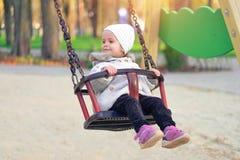 Menina feliz da crian?a no balan?o na queda do por do sol Crian?a que joga no outono no parque natural fotos de stock royalty free