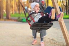 Menina feliz da crian?a no balan?o na queda do por do sol Crian?a que joga no outono no parque natural imagem de stock royalty free