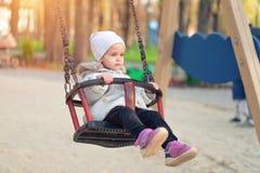 Menina feliz da crian?a no balan?o na queda do por do sol Crian?a que joga no outono no parque natural fotos de stock