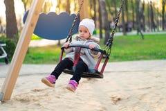 Menina feliz da crian?a no balan?o na queda do por do sol Crian?a que joga no outono no parque natural imagens de stock royalty free