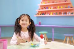 Menina feliz da crian?a pequena que tem o divertimento a pintar na boneca do estuque interno imagem de stock