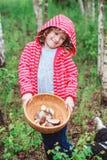 Menina feliz da criança com os cogumelos selvagens comestíveis selvagens na placa de madeira Fotos de Stock Royalty Free
