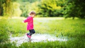 Menina feliz da criança que corre e que salta nas poças após a chuva Imagens de Stock