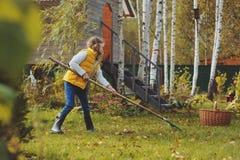 A menina feliz da criança que joga o jardineiro pequeno no outono e que escolhe sae na cesta Trabalho sazonal do jardim Fotos de Stock Royalty Free