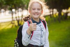 Menina feliz da escola com polegares acima do gesto fotografia de stock royalty free