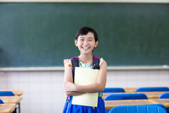 Menina feliz da escola na sala de aula Fotografia de Stock Royalty Free