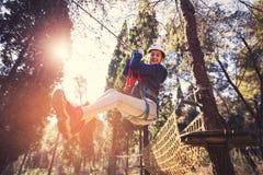 Menina feliz da escola que aprecia a atividade em um parque de escalada da aventura fotos de stock royalty free