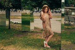 Menina feliz de sorriso no vestido e no chapéu em uma rua da cidade e em olhar a câmera em um chapéu, em um vestido em uma flor e fotografia de stock royalty free