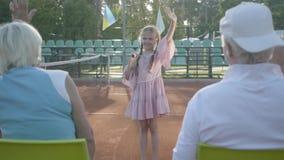 Menina feliz de sorriso pequena bonito com uma raquete de tênis em suas mãos que estão no campo de tênis que olha na câmera filme